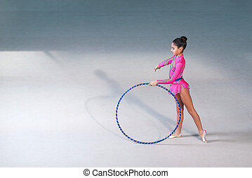 gymnast in a pink suit doing hoop exercise - gymnast in a...