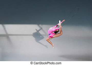 Side view of gymnast in dress with jumping rope - Side view...