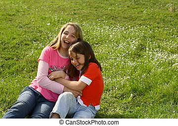 Two sisters tickling each other in the springtime weather -...