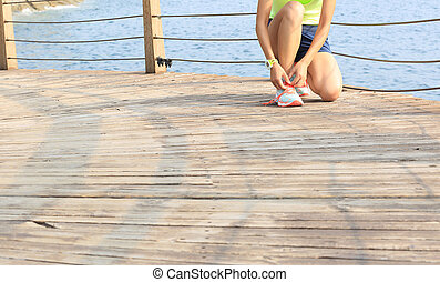 young fitness woman runner tying shoelace at seaside...