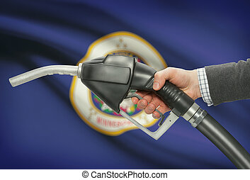 Fuel pump nozzle in hand with USA states flags on background...