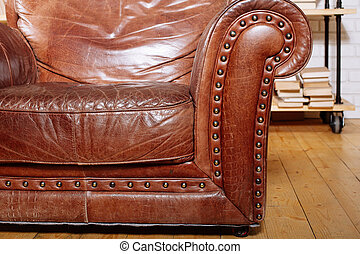 Closeup texture of vintage brown leather armchair in library...