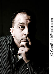 Contemplative Man - High contrast portrait of a middle aged...