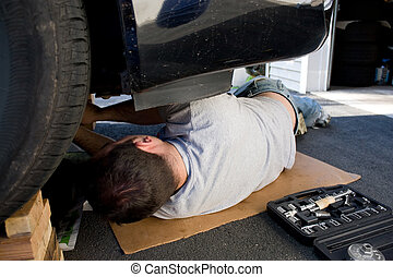 Car Maintenance and Repairs - A young man laying underneath...