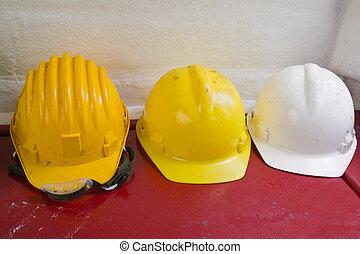 Yellow and white hard hats - Three yellow and white hard...