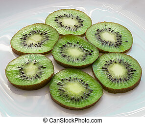 The ripe kiwifruits on the white plate
