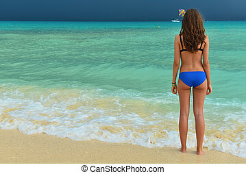 Beautiful girl in a swimsuit on the tropical sea. Woman with a beautiful figure in swimsuit on the beach.