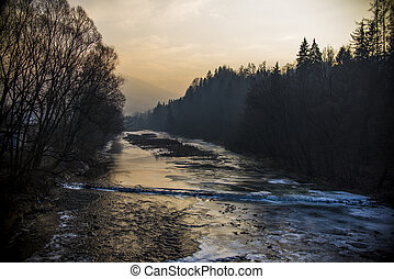 Sunset at a frozen river in the winter