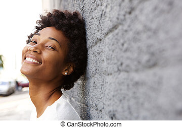 Happy young african woman leaning to a wall - Closeup...