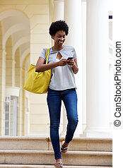 Young african woman sending text message - Full body...