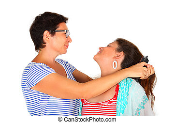 woman brushing her daughters hair against a white background...