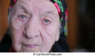 A very old woman. Looking at the camera