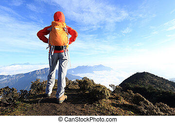 woman hiker hiking on mountain peak