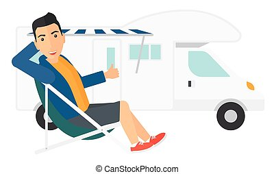 Man sitting in front of motorhome. - A man sitting in a...