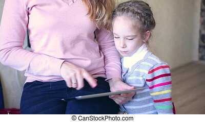 Mother and daughter playing with electronic tablet.