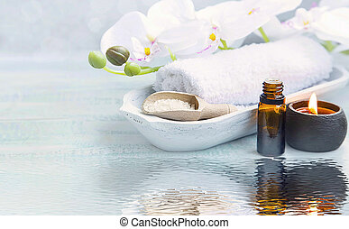 Spa still life with oil and candle on water reflection