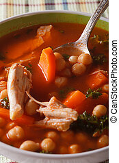 Chickpea soup with chicken close up in a bowl. Vertical -...