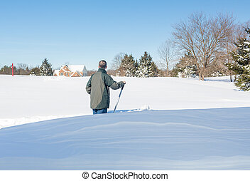 Senior adult man trying to dig out drive in snow - Senior...