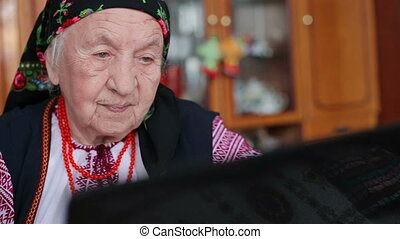 Grandmother watching a movie on a laptop - An elderly woman...