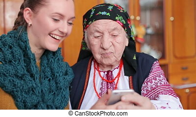 grandmother looking at mobile phone - Granddaughter and...