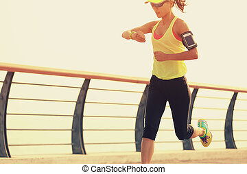 young fitness woman runner checking her running time from...