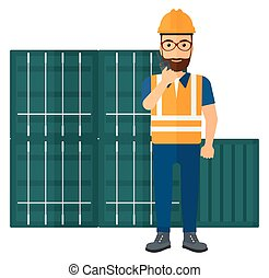 Stevedore standing on cargo containers background - A docker...