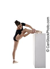 Ballerina put her foot on cube and tying pointes - Ballerina...