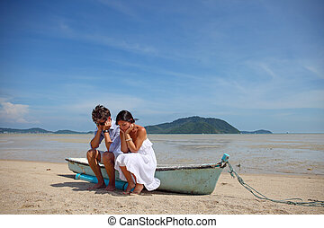 Sad couple on beach - Sad couple sitting on old boat on...