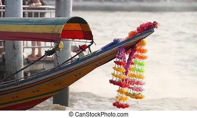 Boat with decorations shakes on waves of Chao-Phraya river....