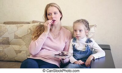 Mother and daughter eat chocolate and watch TV