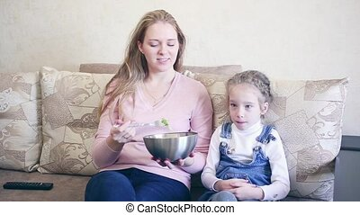 woman with her daughter eat salad