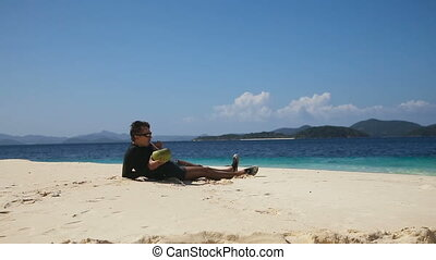 Man on the beach drinking coconut juice - Man drinking...
