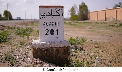 Closeup of distance sign road to Agadir written in French...
