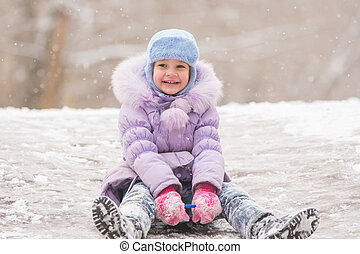 Joyful five years girl rolls down from the icy hill -...