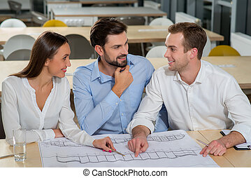 Successful three colleagues are working on plan of building
