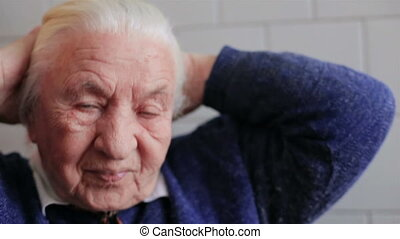A very old woman corrects hair and a smile HD