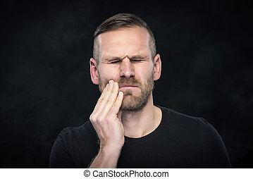 Toothache. Portrait of a man with face closed by hand.
