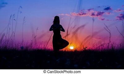 Silhouette of a Young Girl Practicing Yoga Tree Pose At...