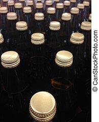 bottles golden caps assorted in lines - Brown ice beer...