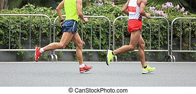 Marathon runners running on city road - Marathon runners...