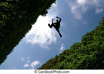 Man jumping over bushes against blue sky background