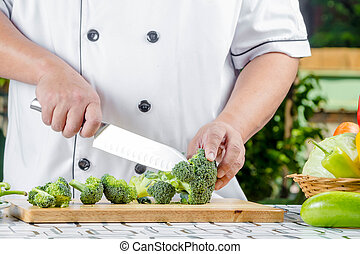 fresh green broccoli - chef cutting fresh green broccoli on...