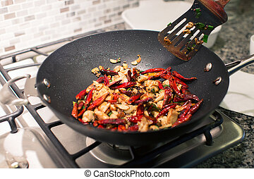 cooking chongqing chicken in wok at home, traditional...