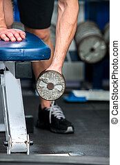 Man working his arms with dumbbells at gym