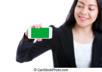 Happy woman showing blank smart phone green screen on white background. Focus on smartphone.
