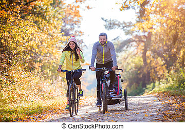 Young family cycling - Beautiful young family with baby in...