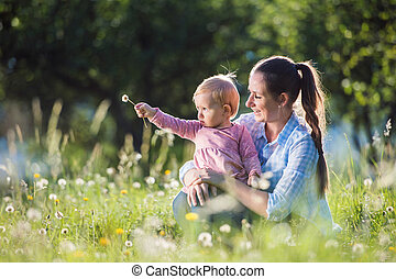 Happy mother and her daughter having fun outside in spring...
