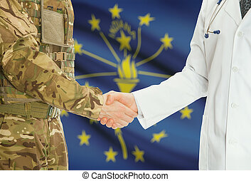 Military man in uniform and doctor shaking hands with US states flags on background - Indiana