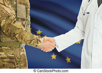 Military man in uniform and doctor shaking hands with US states flags on background - Alaska