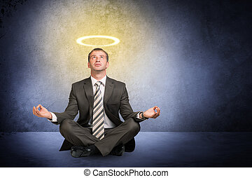 Businessman with nimbus in lotus posture on grey background